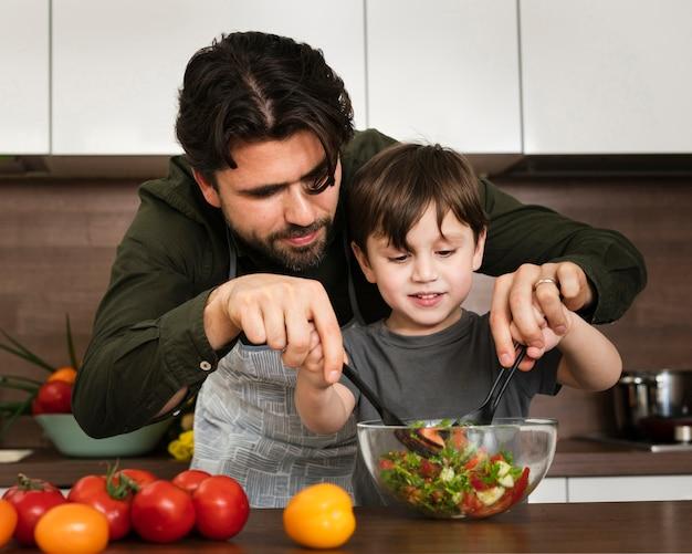 Garotinho, ajudando o pai a misturar salada Foto gratuita