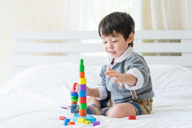 Garotinho alegre com brinquedo de madeira colorido Foto gratuita