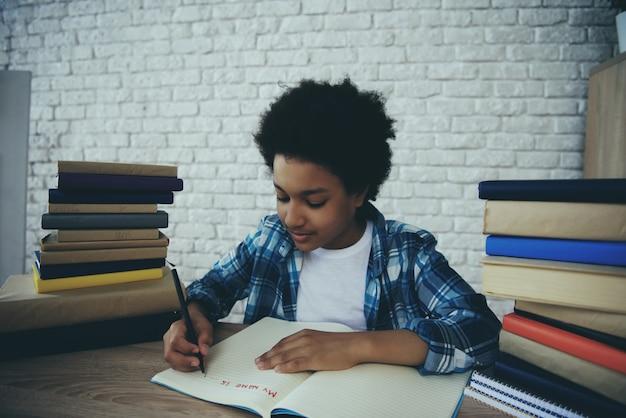 Garotinho americano africano faz lição de casa em casa Foto Premium