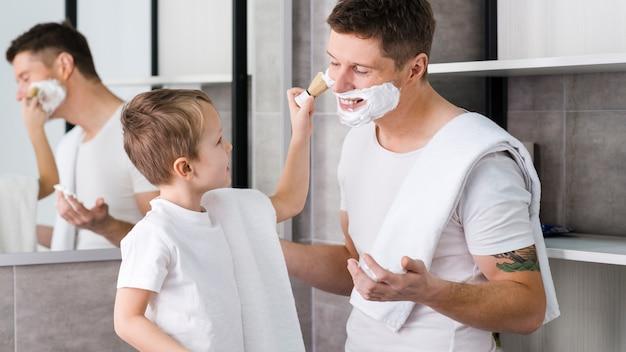 Garotinho, aplicando a espuma de barbear no rosto do pai com escova no banheiro Foto gratuita