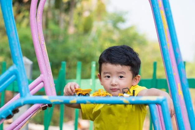 Garotinho asiático jogando slide no parque infantil Foto Premium