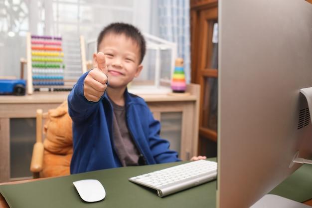 Garotinho asiático sorridente e fofo mostrando o polegar para cima enquanto usa o computador pessoal em casa, menino do jardim de infância estudando online, frequentando a escola via e-learning Foto Premium