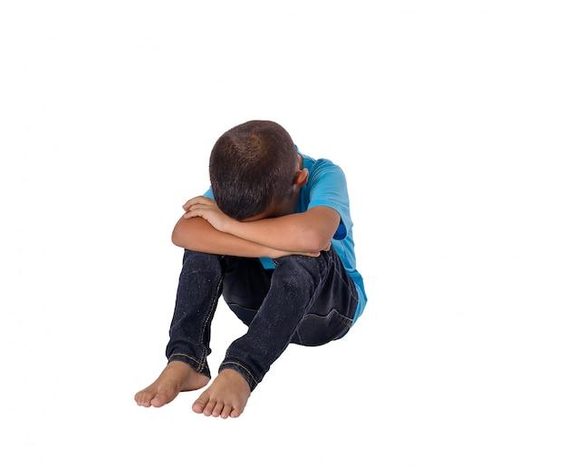 Garotinho asiático triste sentada no chão isolado no branco Foto Premium