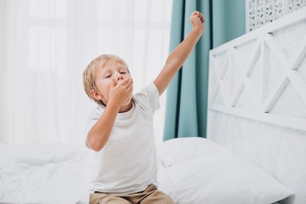 Garotinho bocejando depois de acordar Foto gratuita