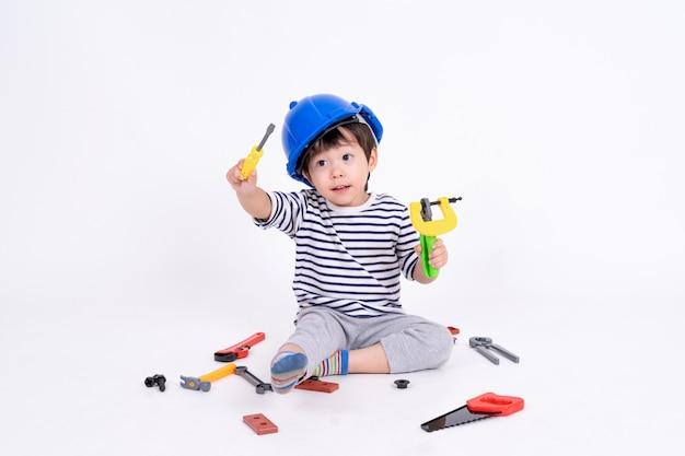 Garotinho brincando com equipamentos de construção em branco Foto gratuita