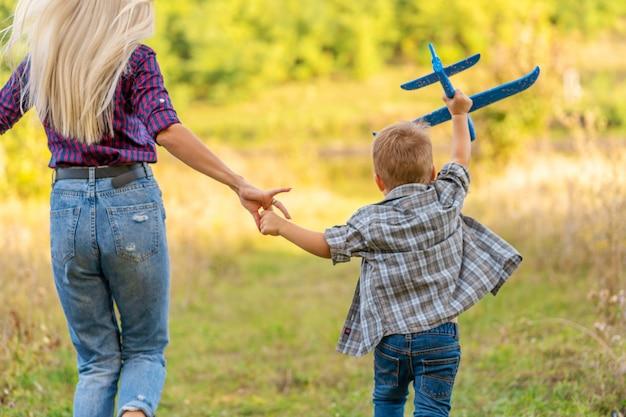 Garotinho brincando com o avião de brinquedo com sua jovem mãe ao ar livre ao pôr do sol. criança feliz é brincar no parque ao ar livre. Foto Premium