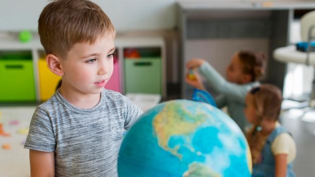 Garotinho brincando com um globo terrestre de frente Foto Premium