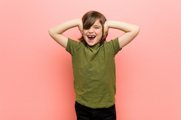 Garotinho, cobrindo os ouvidos com as mãos, tentando não ouvir som muito alto. Foto Premium