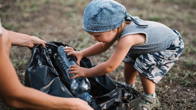 Garotinho, colocando a garrafa de plástico em um saco de lixo Foto gratuita