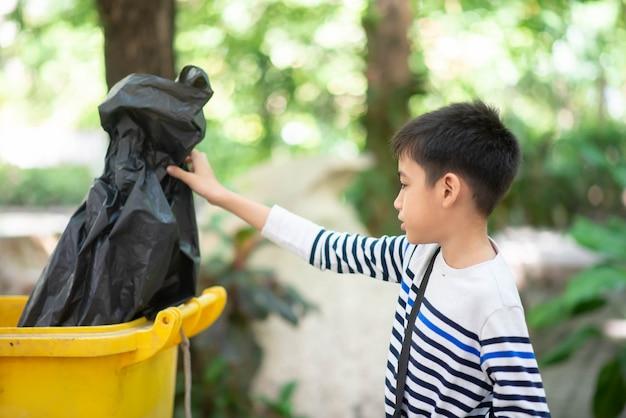 Garotinho colocou o saco de lixo preto no lixo Foto Premium