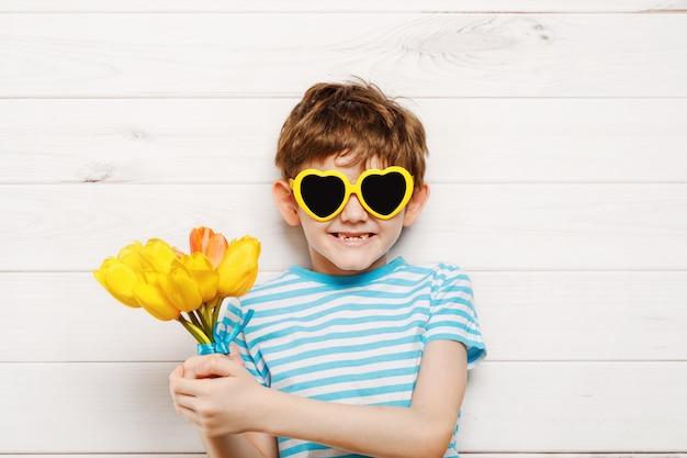 Garotinho com buquê de tulipas. conceito de dia das mães, conceito de férias. Foto Premium