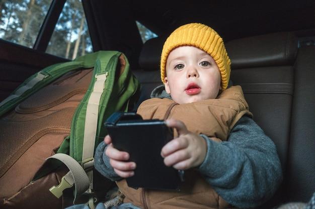 Garotinho com gadget no carro Foto Premium