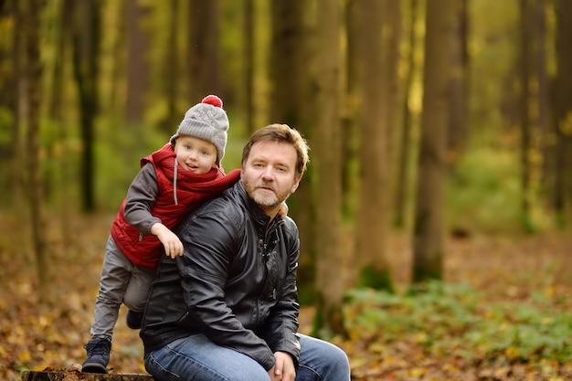 Garotinho com seu pai durante passeio na floresta Foto Premium