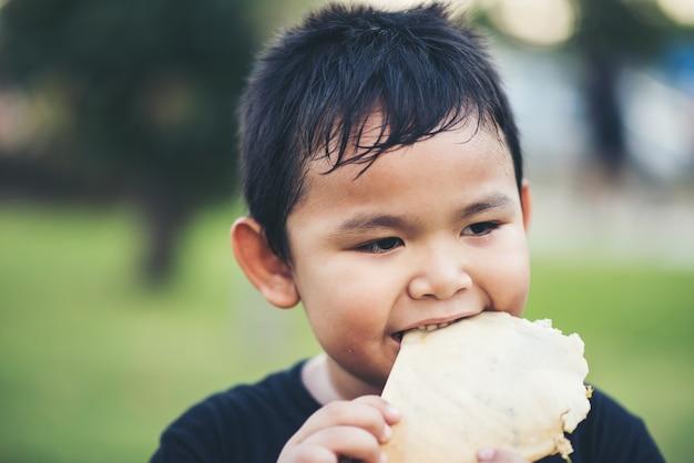 Garotinho comendo comida pão fresco rolo sanduíche Foto gratuita