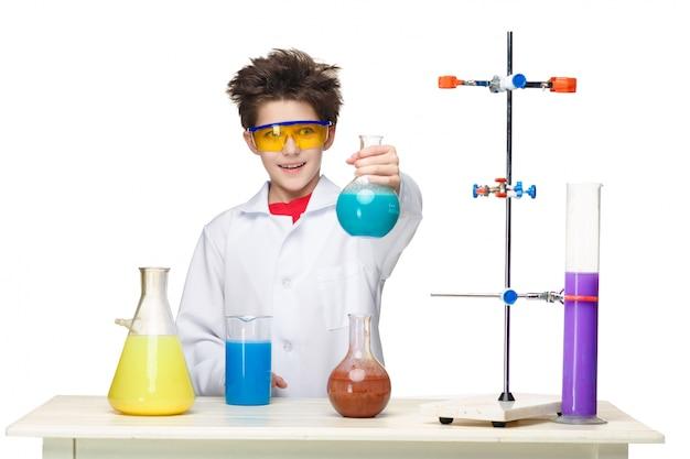 Garotinho como químico fazendo experimento com fluido químico em laboratório Foto gratuita