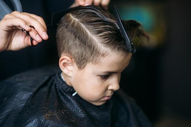 Garotinho, cortando o cabelo pelo barbeiro enquanto está sentado na cadeira na barbearia. Foto Premium