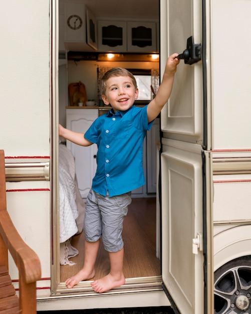Garotinho dando uma olhada atrás da porta de seu trailer Foto gratuita