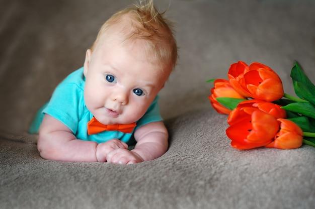Garotinho deitado na cama e buquê de tulipas Foto Premium