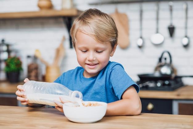 Garotinho, derramando leite na tigela de cereais Foto gratuita
