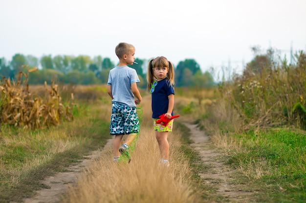 Garotinho e menina jogando fora na estrada de cascalho de campo em um dia ensolarado de verão Foto Premium