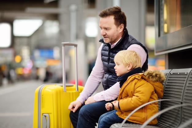 Garotinho e seu pai esperando trem expresso na plataforma da estação ferroviária ou esperando seu voo no aeroporto Foto Premium