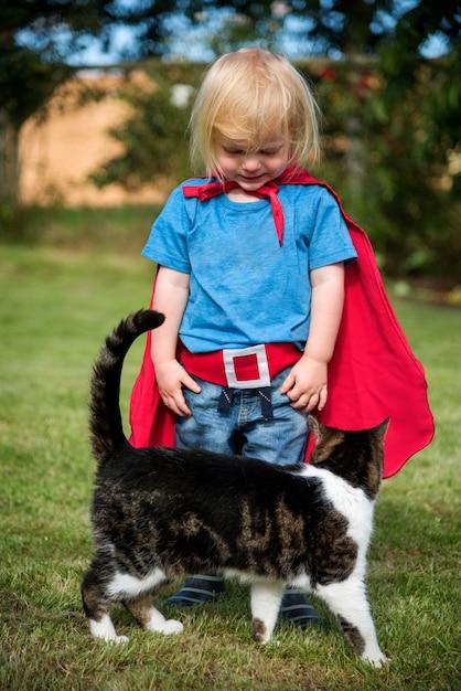 Garotinho em traje de super-heróis com seu gato em um quintal Foto gratuita