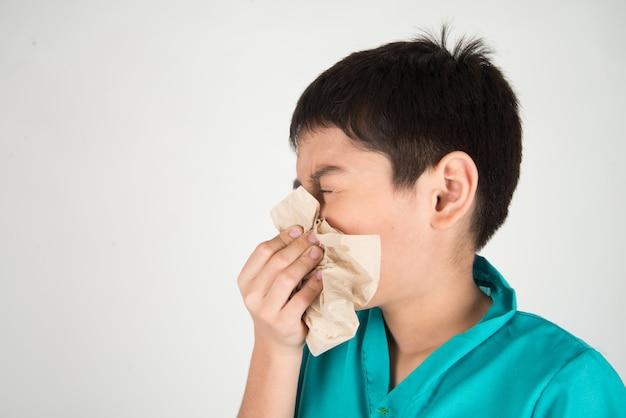 Garotinho está espirrando e tosse da gripe usando o tecido limpo Foto Premium