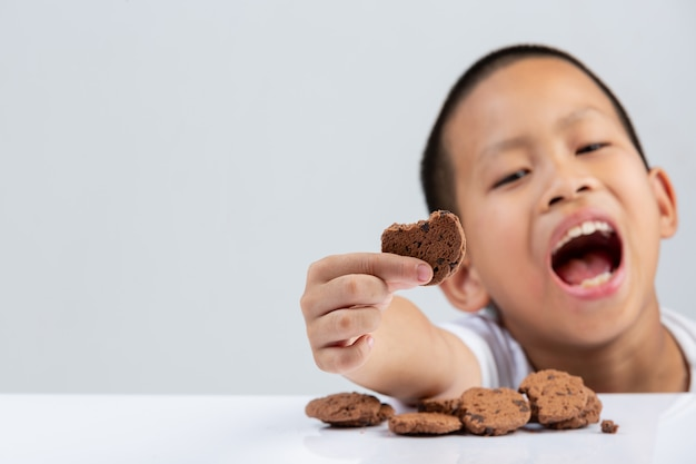 Garotinho está segurando o biscoito quer comer na mesa na parede branca. Foto gratuita