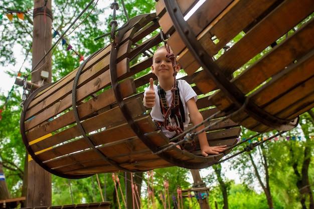 Garotinho executa uma pista de obstáculos em um parque de corda Foto Premium