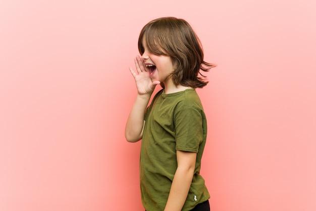 Garotinho, gritando e segurando a palma da mão perto da boca aberta. Foto Premium