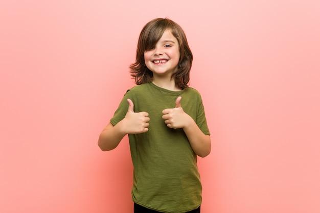 Garotinho, levantando os dois polegares, sorrindo e confiante. Foto Premium