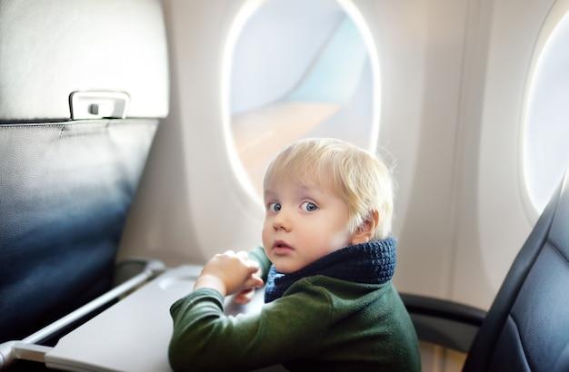 Garotinho medo sentado pela janela do avião durante o vôo Foto Premium