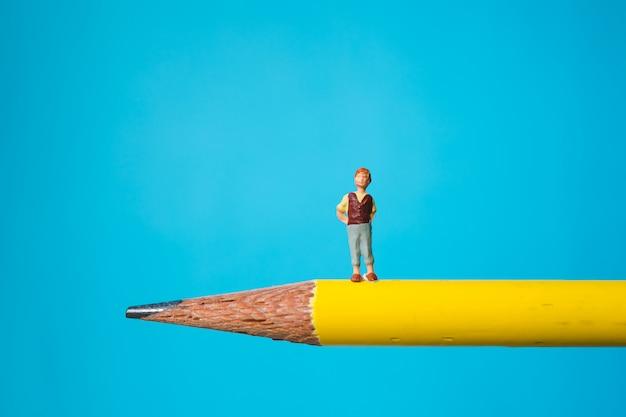 Garotinho miniatura em pé no lápis amarelo usando como conceito de família e educação Foto Premium