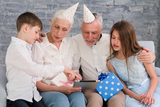 Garotinho mostrando algo para sua família na tabuleta digital Foto gratuita