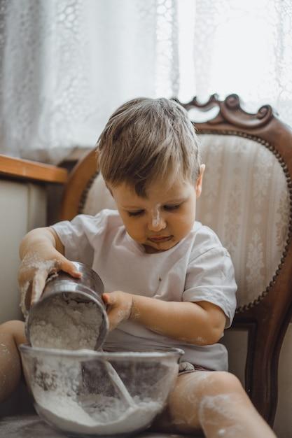 Garotinho na cozinha ajuda a mãe a cozinhar. a criança está envolvida na culinária. Foto gratuita
