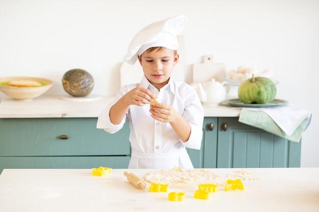 Garotinho na fantasia de cozinheiro assando biscoitos Foto Premium