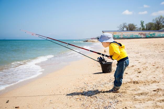 Garotinho na praia de areia Foto Premium