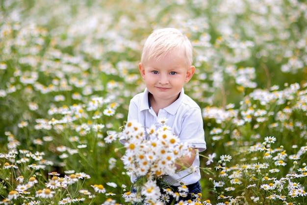Garotinho no campo da margarida com um buquê de flores silvestres Foto Premium