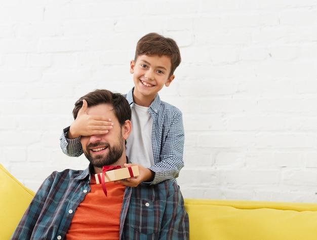 Garotinho, oferecendo um presente para seu pai Foto gratuita