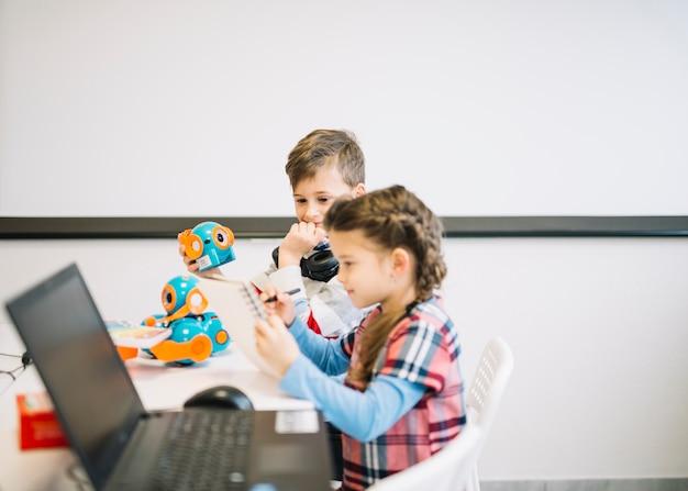 Garotinho olhando menina no caderno de desenho com caneta na sala de aula Foto gratuita