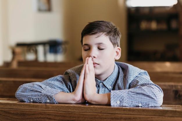 Garotinho orando na igreja Foto gratuita
