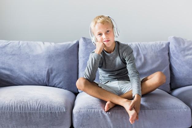 Garotinho, ouvindo música em casa Foto gratuita