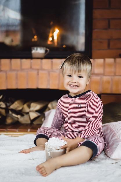 Garotinho pelo fogo e com chocolate quente com marshmallows Foto gratuita