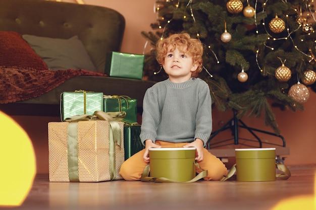 Garotinho perto de árvore de natal em um suéter cinza Foto gratuita