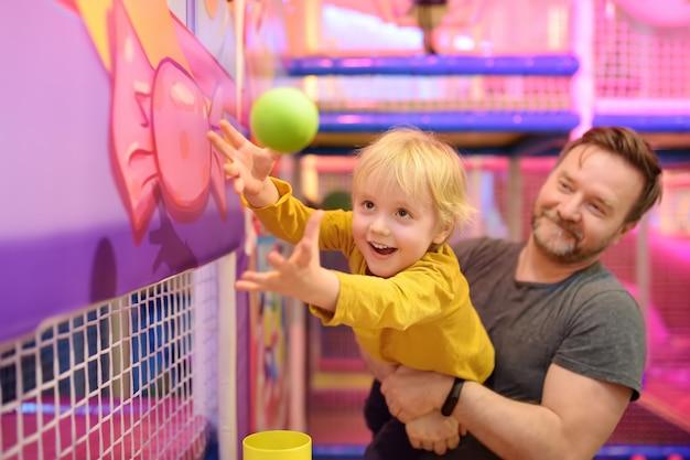 Garotinho se divertindo em diversão no play center. garoto jogando pela bola mágica. Foto Premium