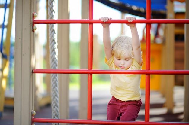 Garotinho se divertindo no playground ao ar livre. lazer esportivo de verão para crianças Foto Premium