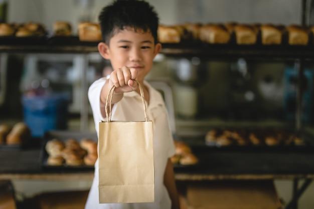 Garotinho segurando a loja de padaria de fundo de papel de saco Foto Premium