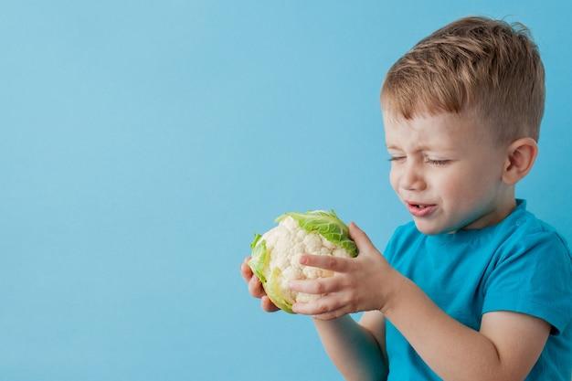 Garotinho segurando brócolis nas mãos sobre fundo azul, dieta e exercício para o conceito de boa saúde Foto Premium