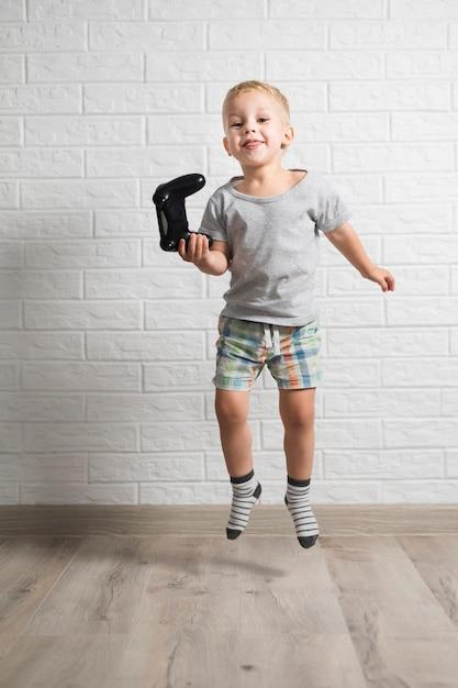Garotinho segurando o joystick e pulando Foto gratuita