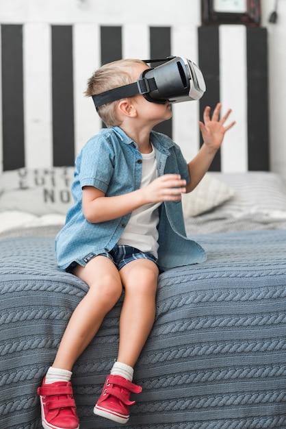 Garotinho sentado na cama usando óculos de realidade virtual Foto gratuita